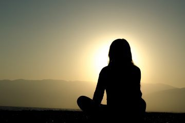 Silhouette of woman sitting and meditating at sunset - What is the meaning of life?