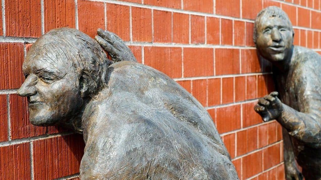 sculpture art men listening at wall