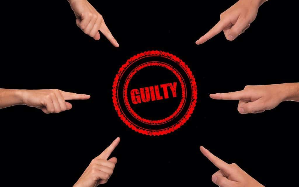 hands pointing to word 'guilty'