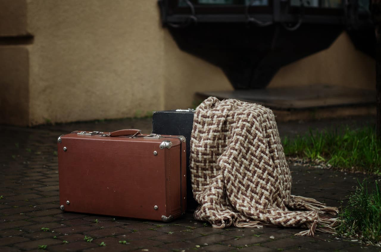 Two suitcases and blanket in rain - Acceptance is tricky