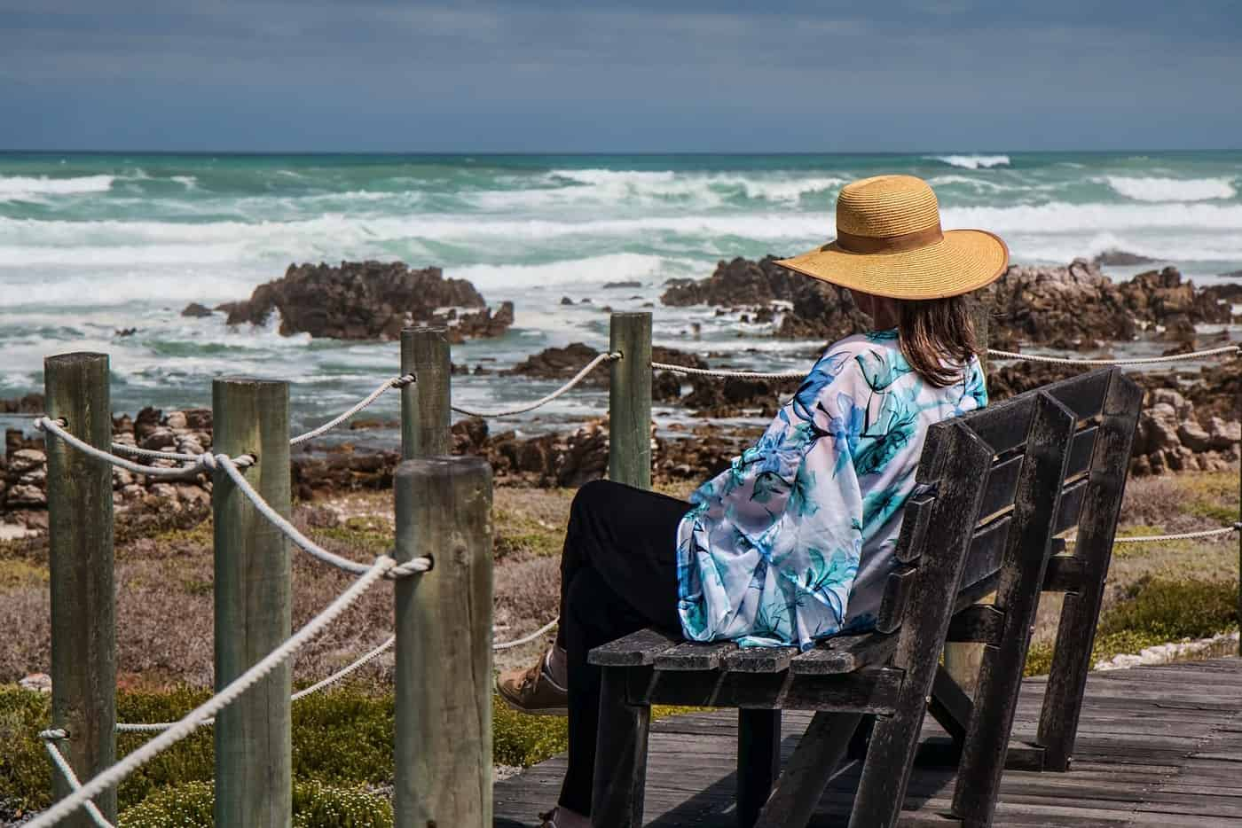 woman resting on bench next to sea