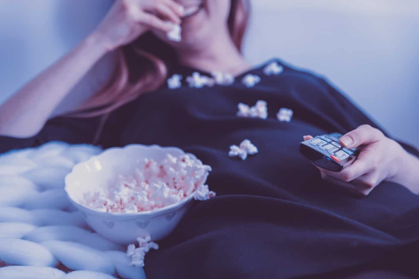 Young woman eating popcorn in bed - Making fat