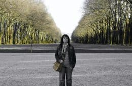Down-to-earth woman standing in front of blurred trees - A minimalist's guide to enlightenment