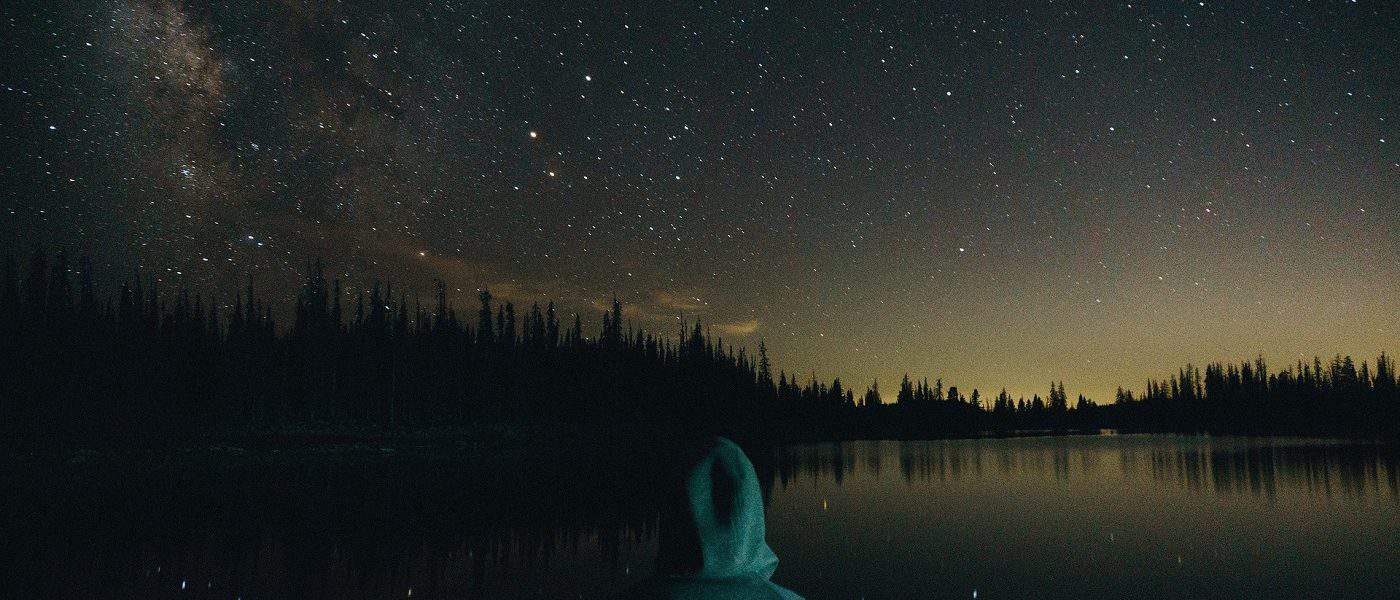 Hooded person thinking in front of starry sky and water - War trauma therapy