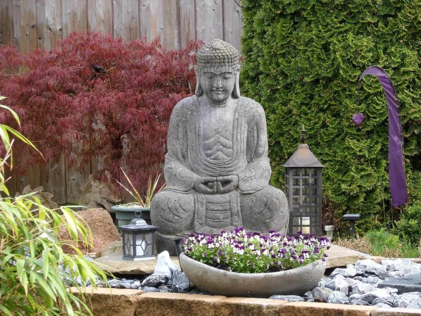 Buddha statue, lanterns and flowers outdoors - 4 basic stages of meditation