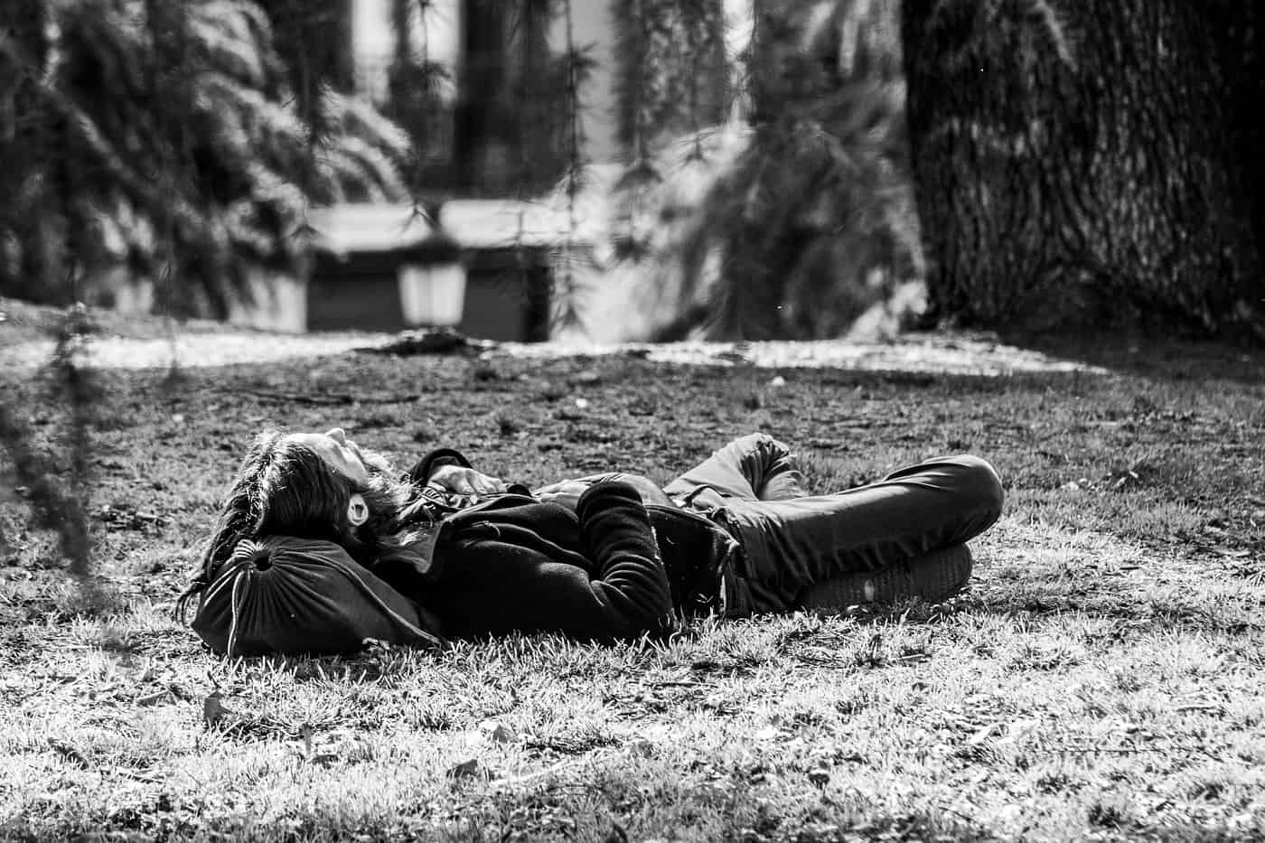 Man lying on grass with head on bag - Poems by Mike Larcombe
