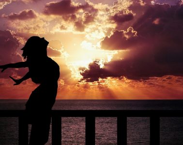 Silhouette of woman at sunset with arms outstretched, face to sky - Put on your oxygen mask