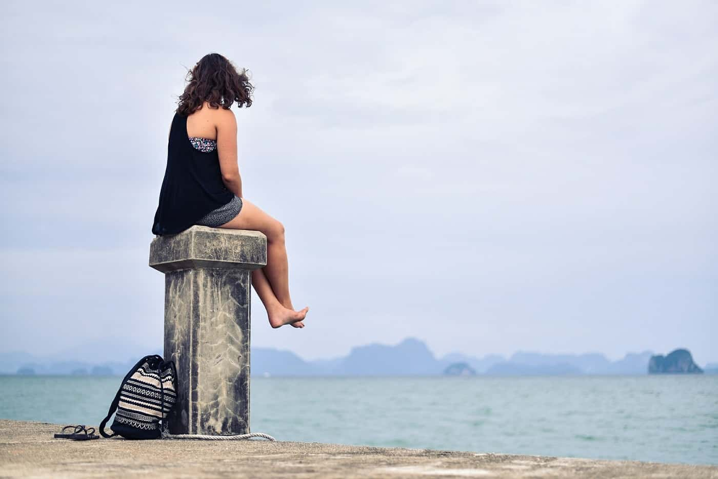 Woman sitting on pillar on quiet beach - Silence