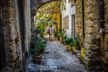 Woman walking alone on cobblestone path - The solo traveler's handbook
