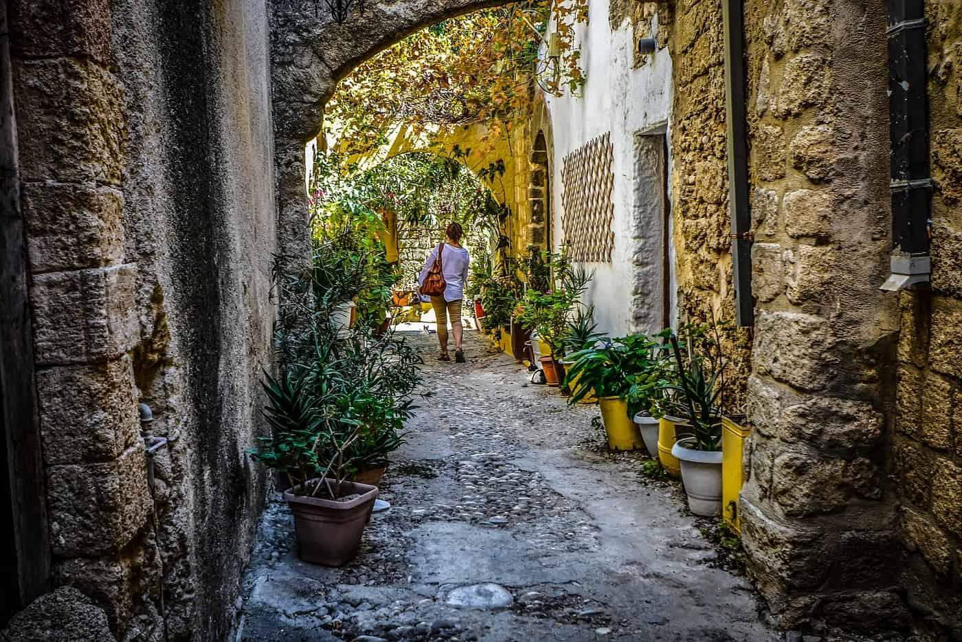 Woman walking alone on cobblestone path - The solo traveler's handbook