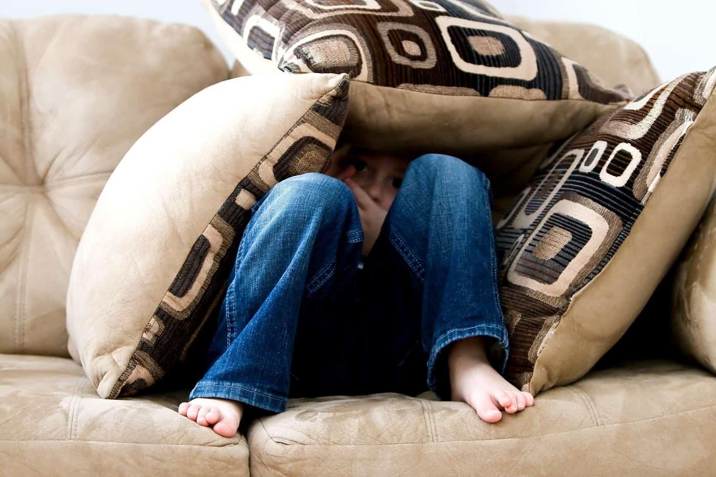 Little boy hiding under throw pillows - Family myths
