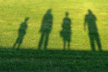 Shadow of family of four in grass - Family myths