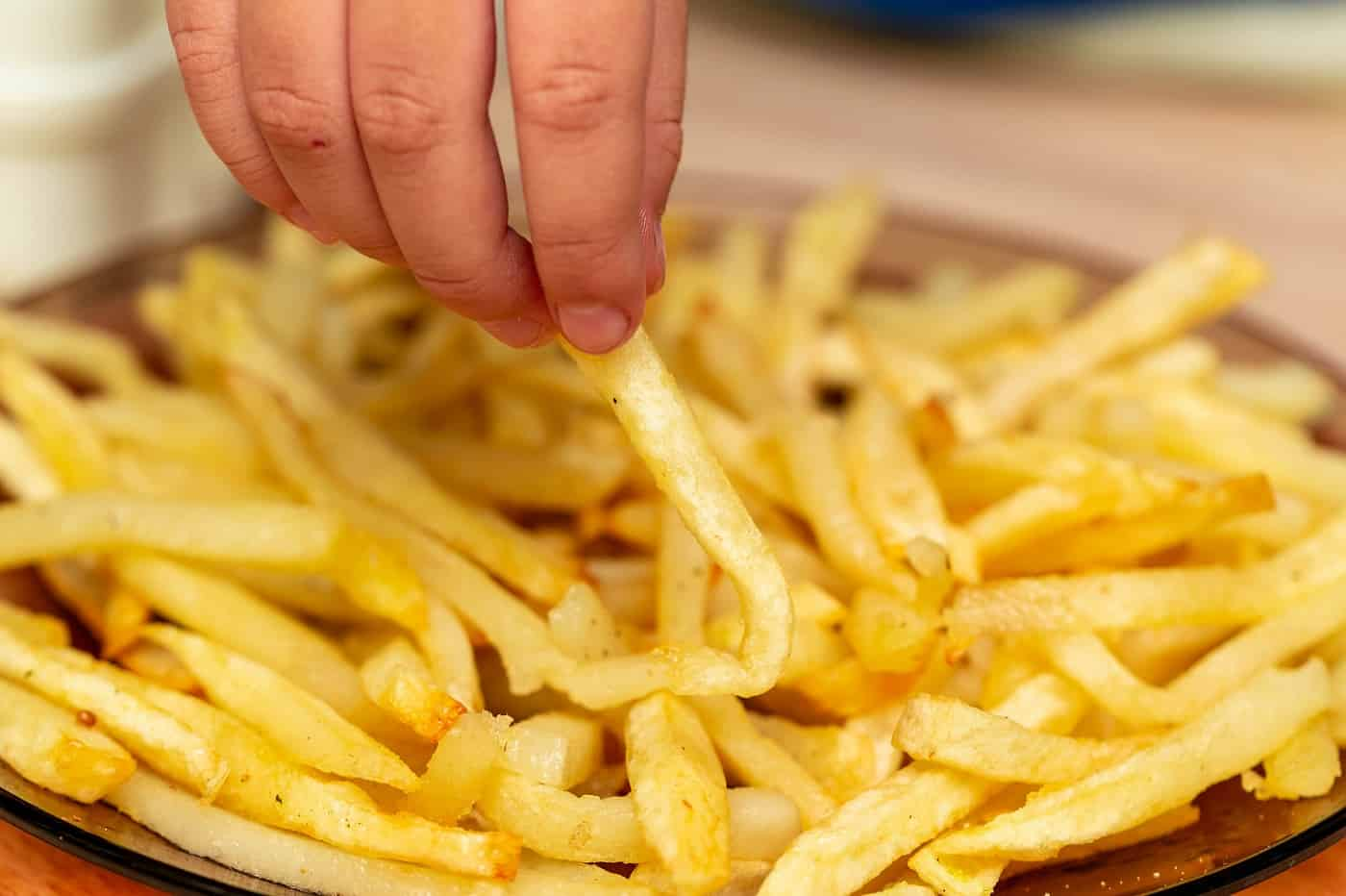 Person's hand reaching for French Fries - Real food vs. fake food
