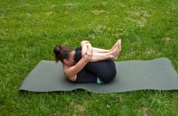 Woman doing Yoga on mat, on grass - Rise and shine