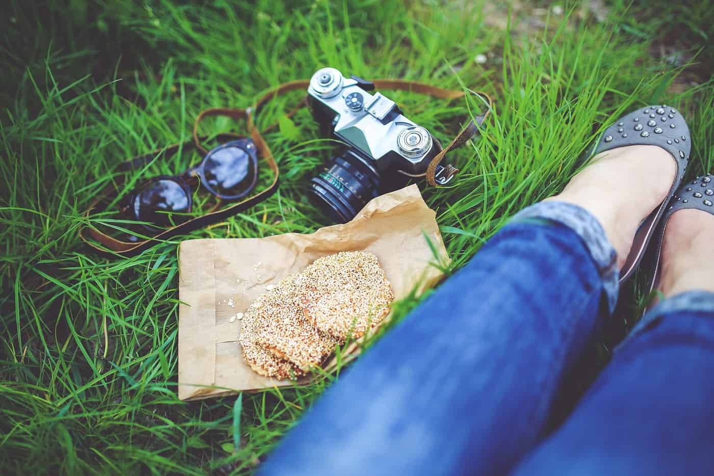 Woman sitting in grass next to two cookies - Self-trust and compassion