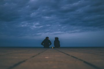 Couple sitting on cement outdoors underneath dark blue sky - Poems by Mike Larcombe