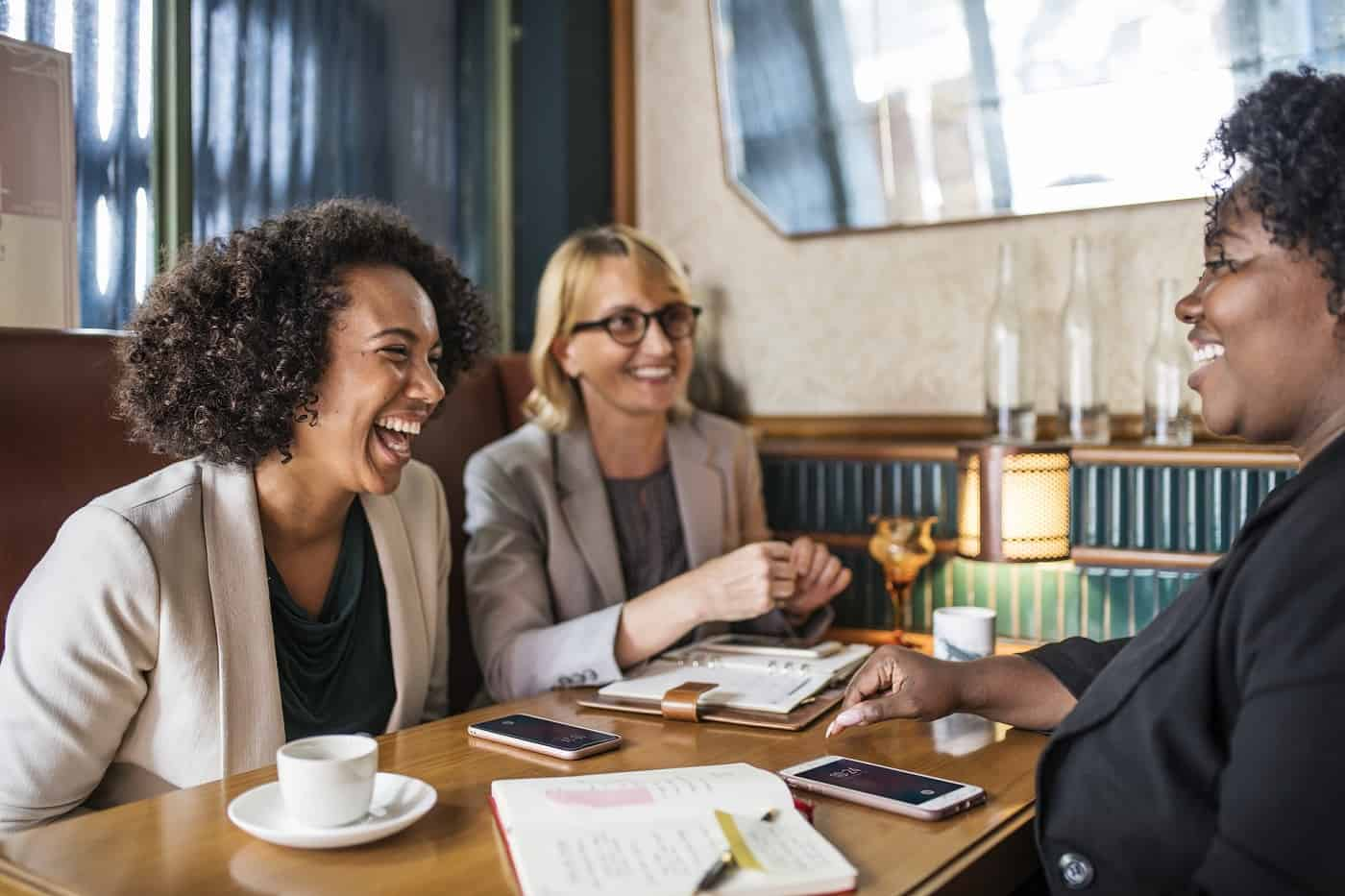Three women talking and laughing over coffee
