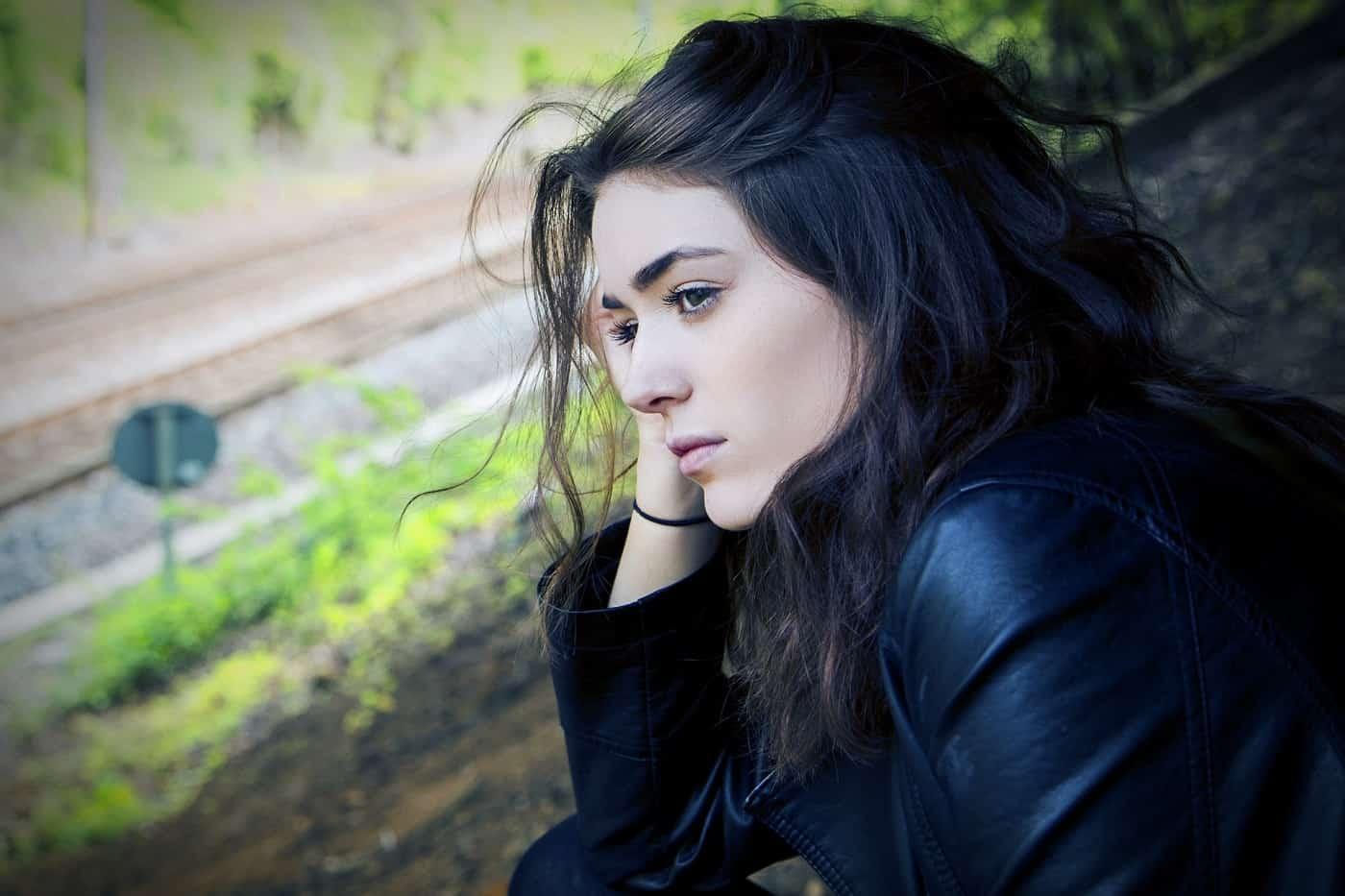 Sad brunette woman sitting outside