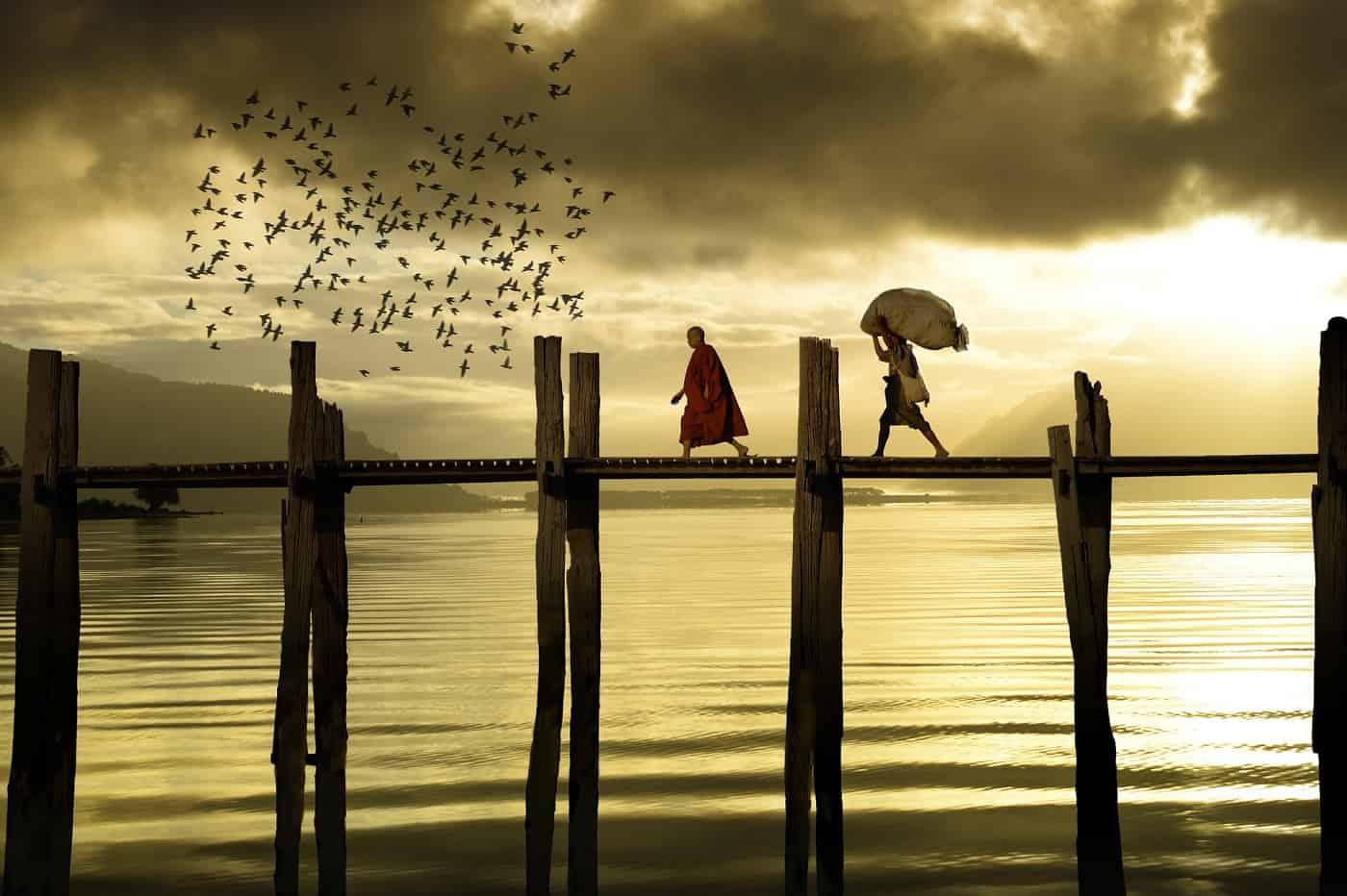 Monk and layman walking across bridge