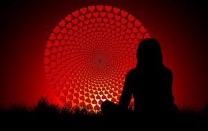 Woman meditating in front of wheel of hearts