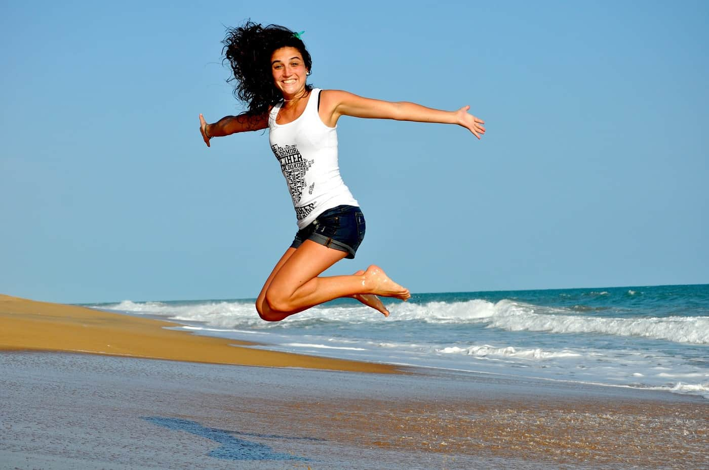 Woman jumping high on beach
