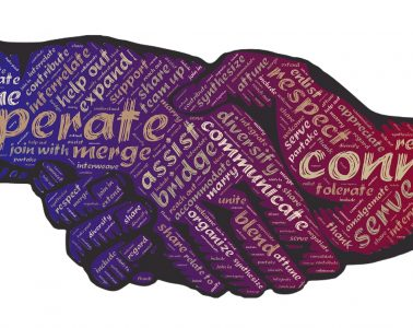 Two hands with co-operative words on them shaking each other