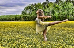 Woman balancing on one leg in field