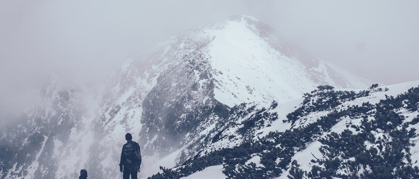 Two people partway up a mountain with a snow-capped peak