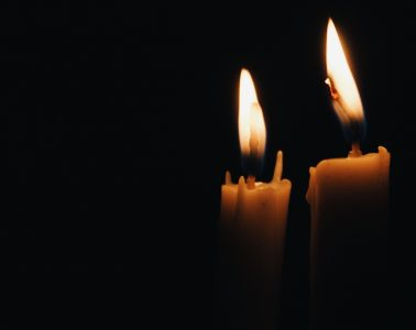 Two yellow candles against black background