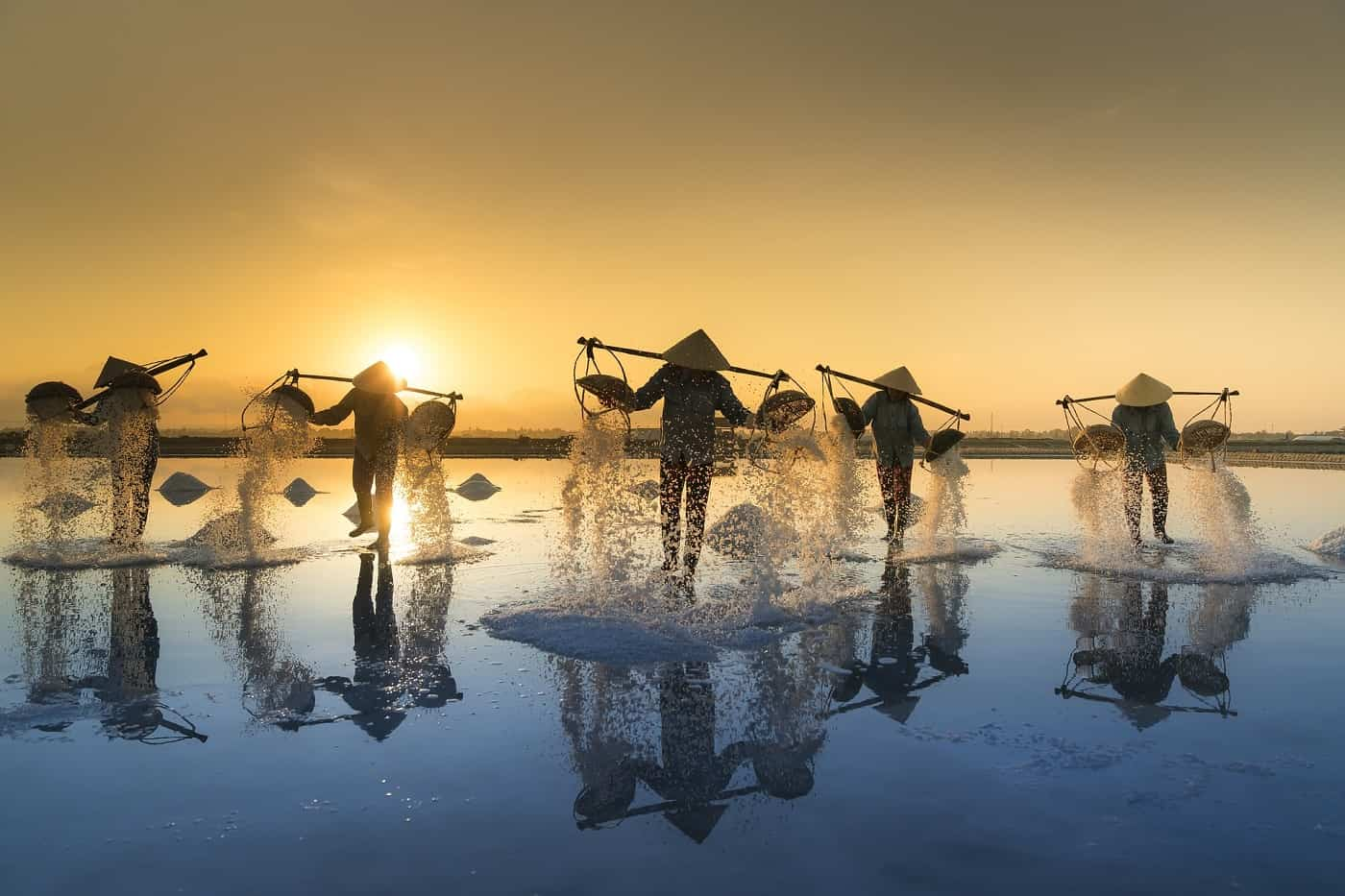 A few people harvesting salt from water