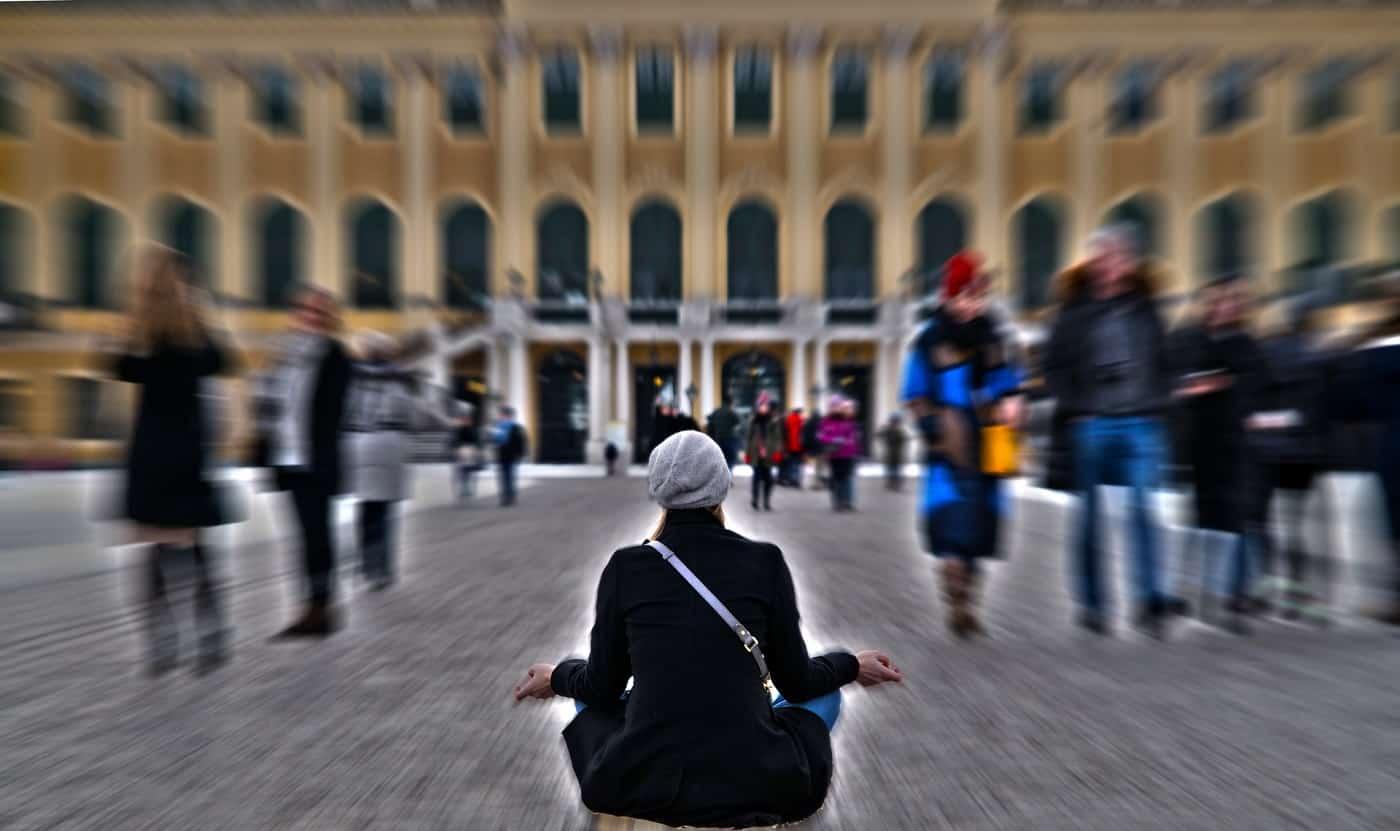 Person meditating on city street