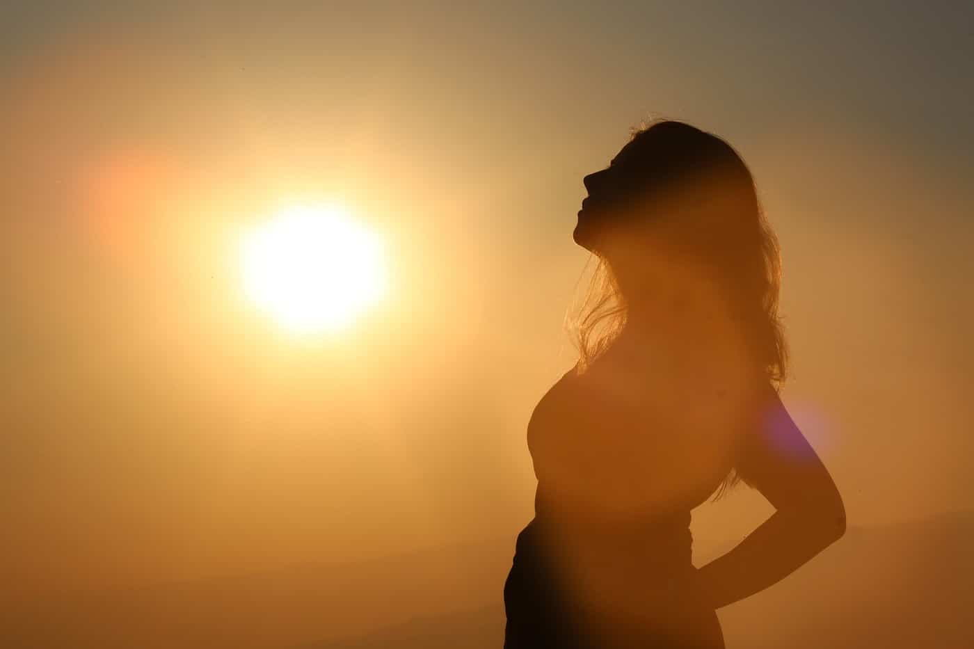 Woman's silhouette looking up at sun