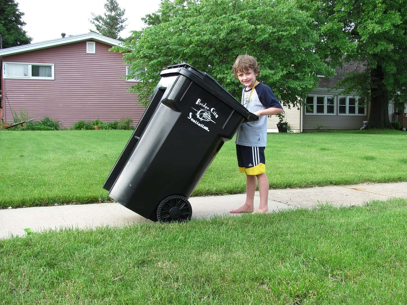 Young boy pushing trash can