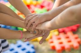 Group of children stacking hands
