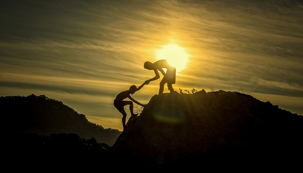 man helping another up a hill