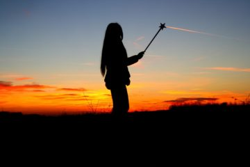 Silhouette of girl with magic wand in hand