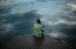 Woman sitting on dock next to lake