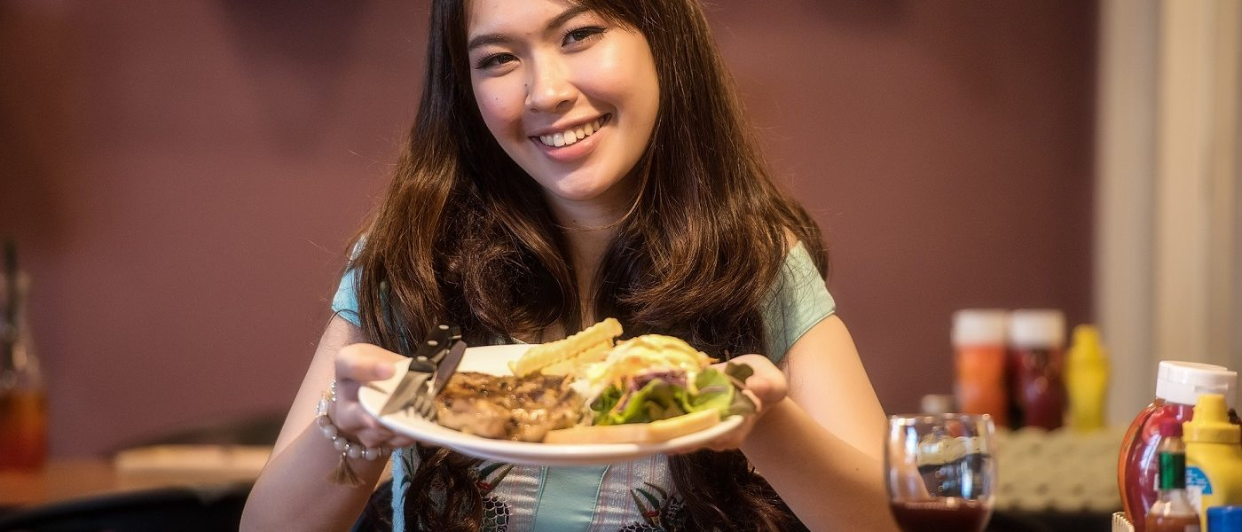 Woman holding out plate of food