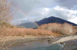 Rainbow against mountain, both next to water