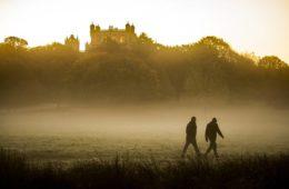 Two people walking outdoors in mist