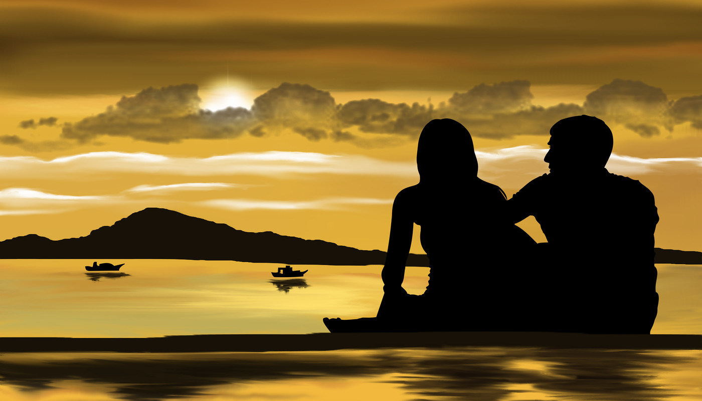 two people sitting on a beach