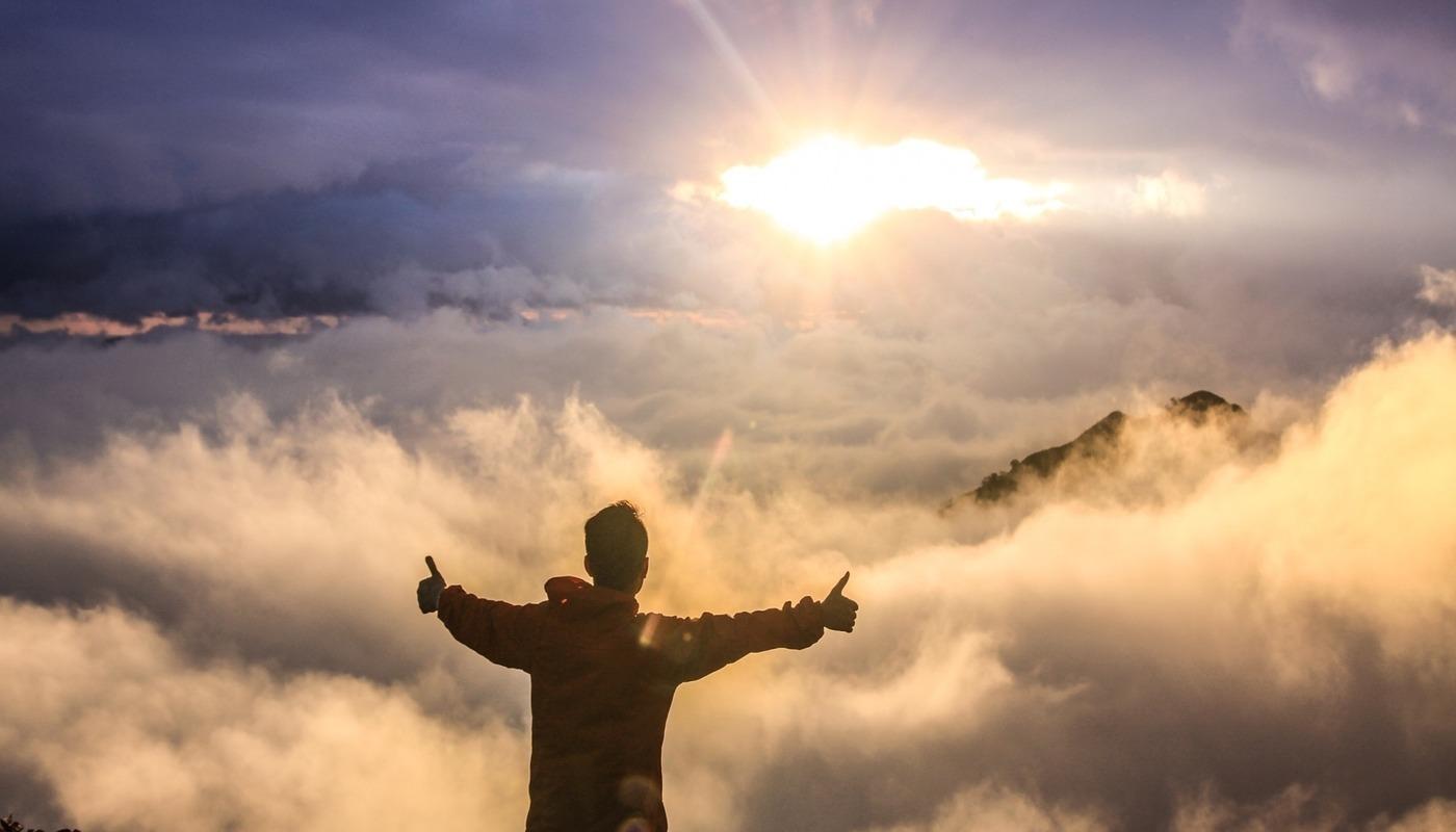 man on mountain embracing the sun