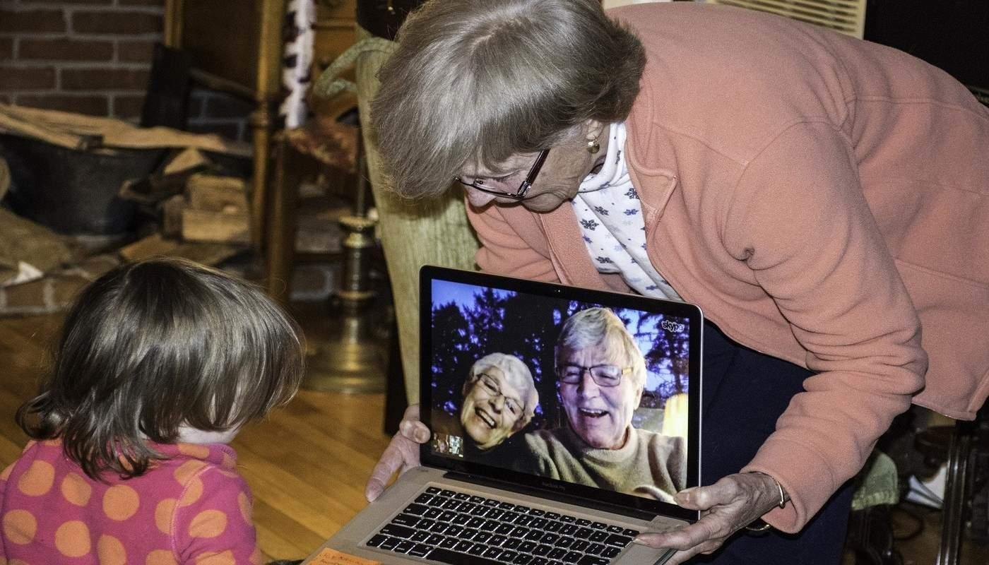 little girl speaking to her grandparents via laptop