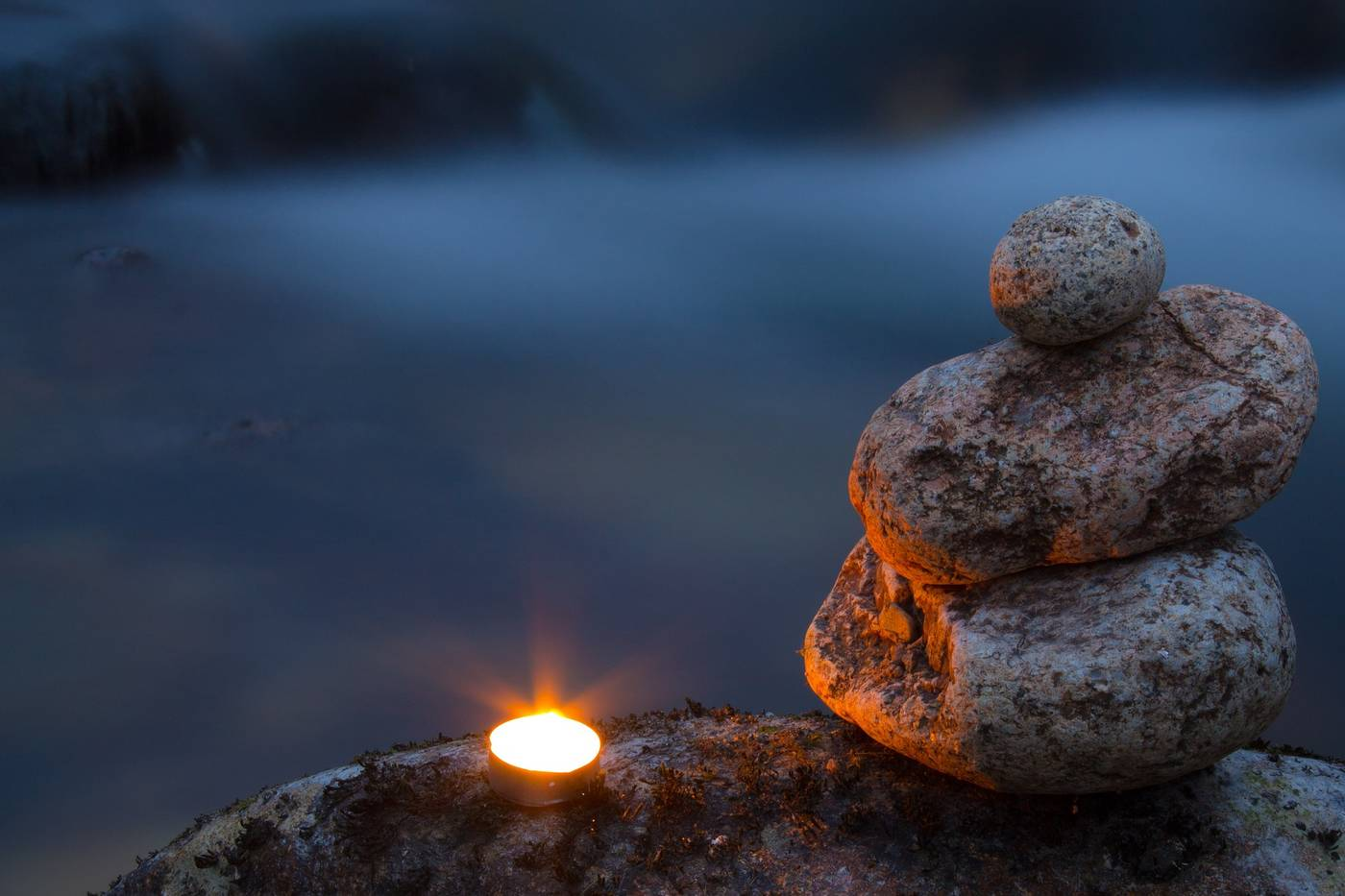 Lit candle next to Zen stones