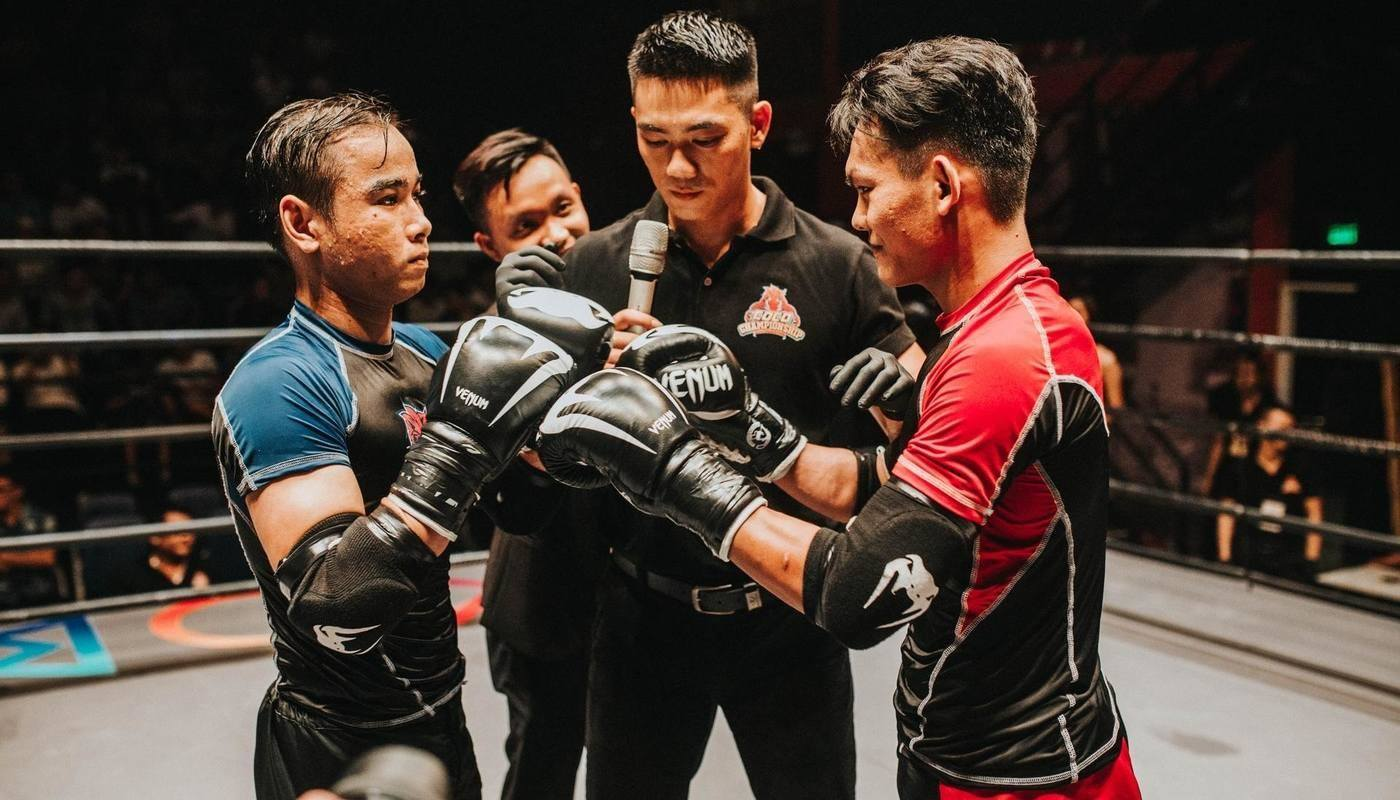 boxers in middle of ring with referee