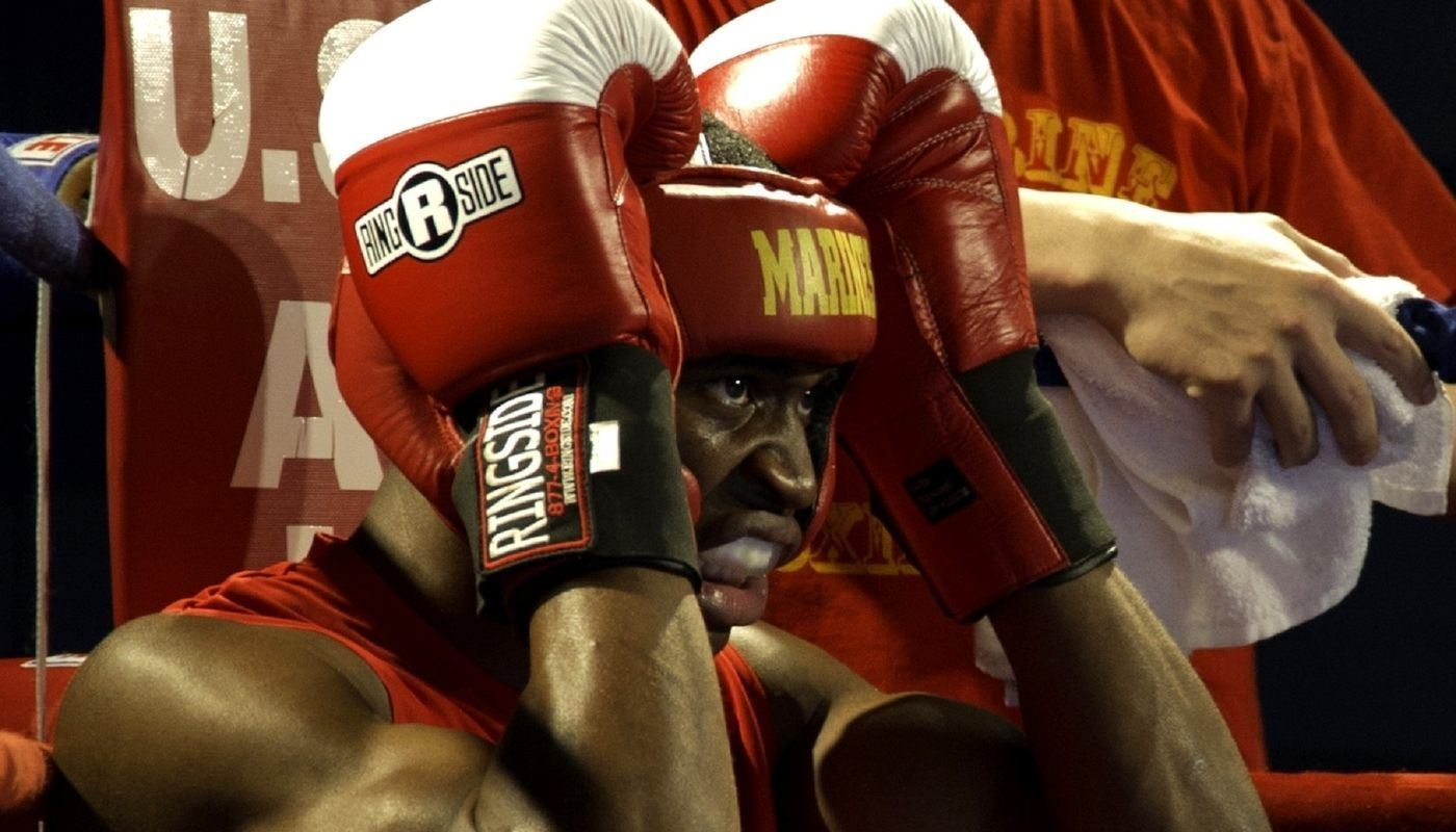 boxer in red in his corner, holding his head