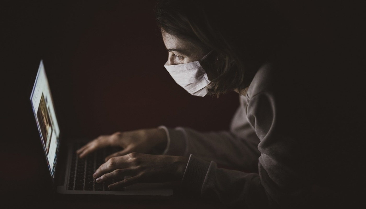woman with surgical mask in front of laptop