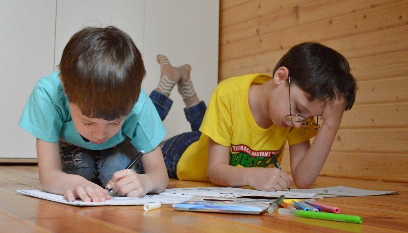 two young boys colouring on the floor