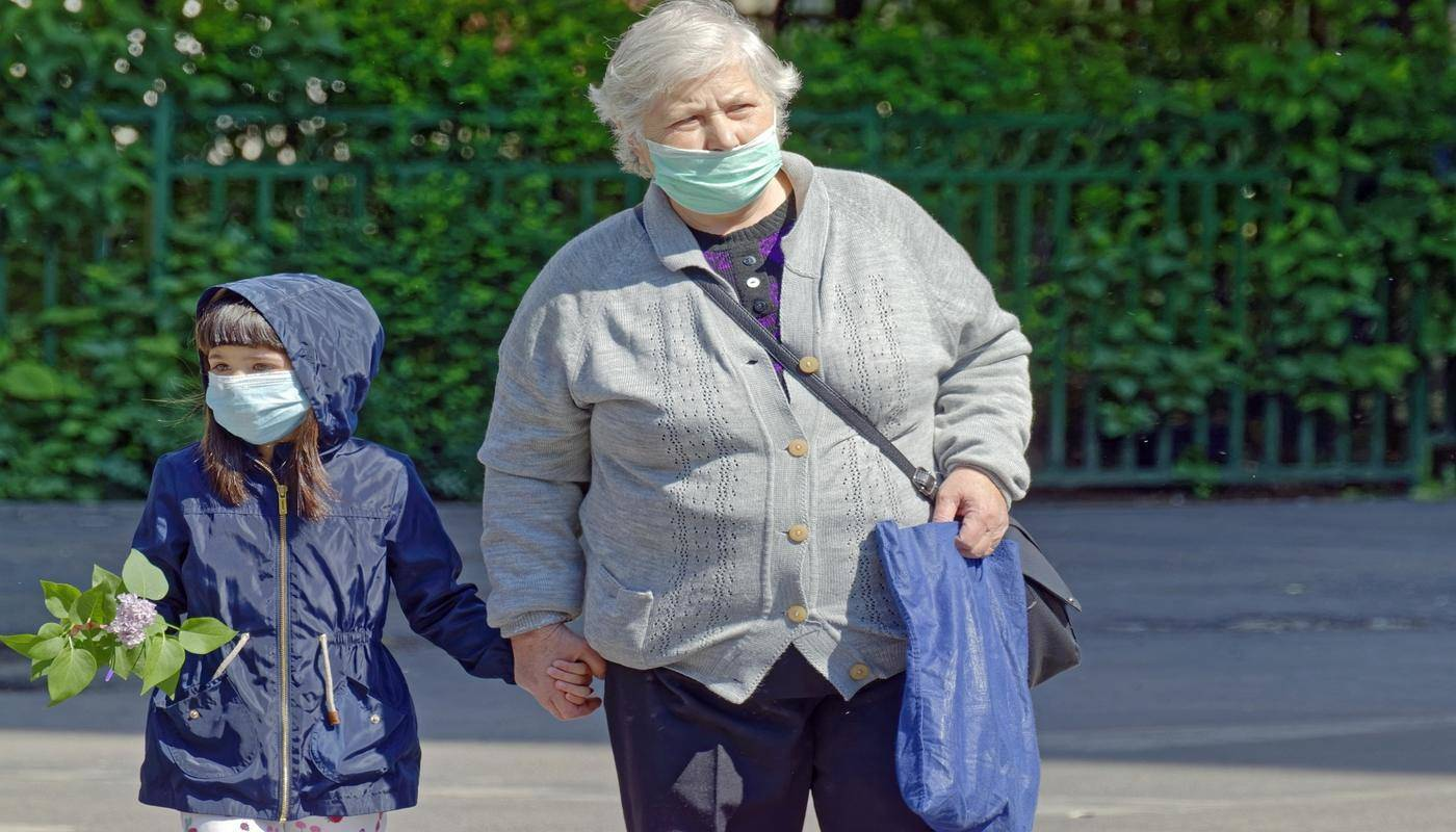 woman and granddaughter shopping with masks